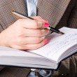 Businesswoman hand with pen and notebook — Stok fotoğraf