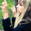 Young woman holding on fence - Stock Photo