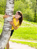 Young cheerful woman hold on birch — Stock Photo