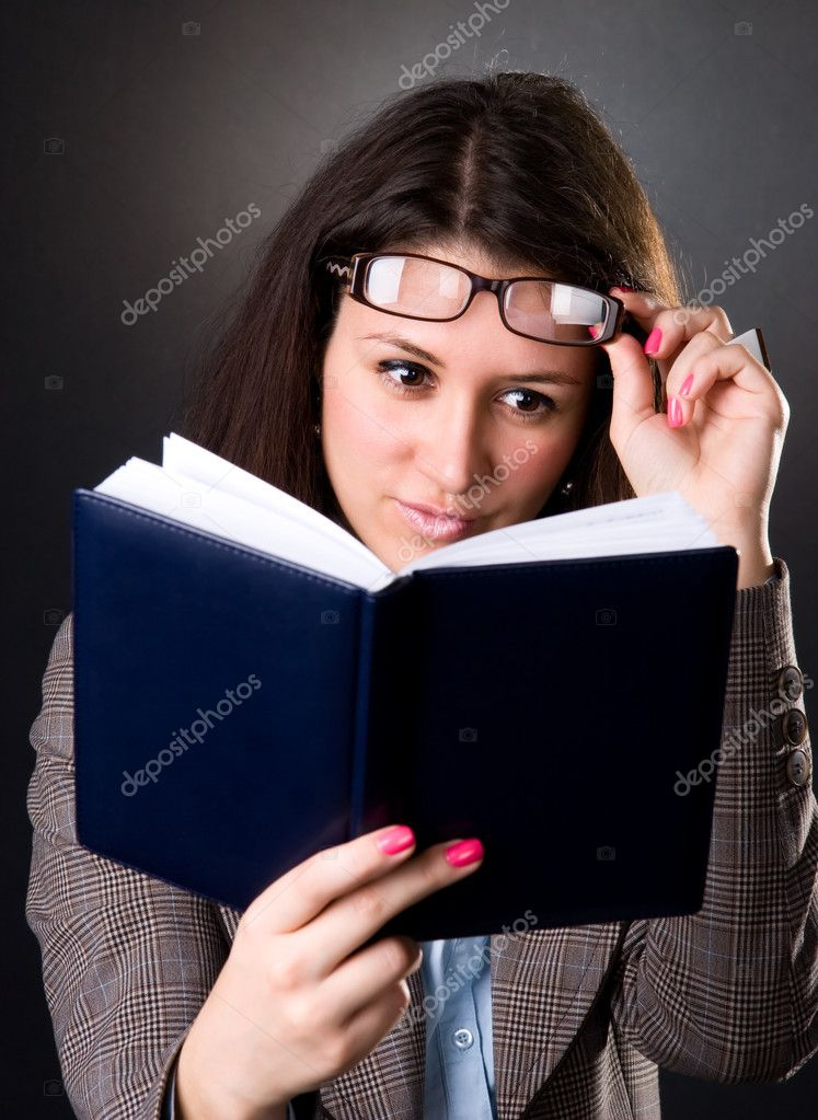 Young school teacher reading a book. On dark background. — Stock Photo #1752139