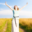 Young happy woman walking on a field — Stock Photo