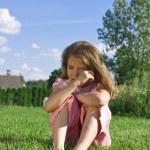 çimlerde oturan küçük kız ağlıyor — Stok fotoğraf