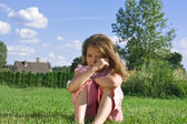 Crying little girl sitting on grass — Stock Photo