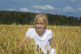 Young teenager girl sit on wheat — Stock Photo