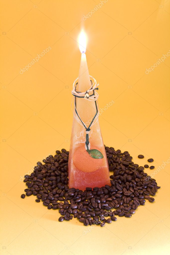 Orange candle with coffee beans on yellow background — Stock Photo #1133797