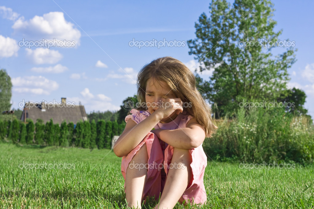 Crying little girl sitting on grass — Stock Photo #1134225
