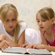 Two sisters reading book — Stock Photo
