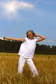 Beautiful teenager girl dancing on wheat — Stock Photo