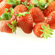 Lots of fresh strawberries over white — Stock Photo
