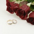 Two wedding rings with three red beautif — Stock Photo