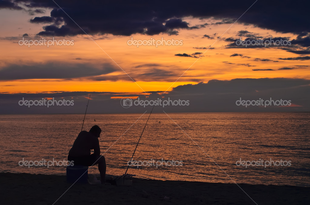 A fisherman on the beach. Fishing at sunset. — Stock Photo #1470508