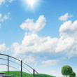 Stock Photo: Green avenue on blue sky under sun.