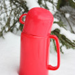 Thermos in a snowdrift - Stock Photo
