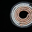 Circle of white, black and pink pearls o - Stock Photo