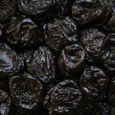 Dry plums or prunes fruit as background — Stock Photo