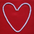 Heart from white pearls on a red silk — Stock Photo