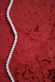 White pearls on a terracotta velvet — Stock Photo