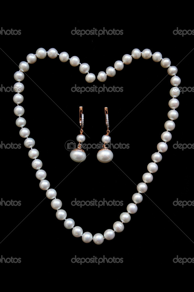 Necklace of white pearls and golden earrings with diamonds and pearls on the black velvet — Stock Photo #1824232