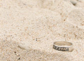 Silver ring lays on sand — Stock Photo