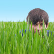 Young man hiding in green grass — Stock Photo