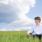 Businessman sitting on grassland — Stock Photo