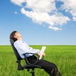 Businessman relaxing on grassland — Stock Photo