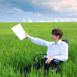 Businessman working on grassland — Stock Photo