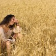 Attractive girl sitting in golden wheat — Stock Photo