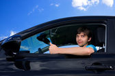 Successful young man sitting in own car — Stock Photo