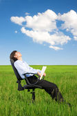Businessman relaxing on grassland — Stock Photo