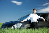 Businessman with car on grassland — Stock Photo