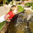 Stock Photo: Cute little girl near a fountain