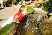 Cute little girl near a fountain — Stock Photo