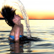 Girl splashing  at sunset - ストック写真