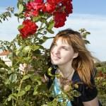 Pretty woman in roses garden — Stock Photo