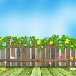 Wooden fence with a flower garland - Stock Photo