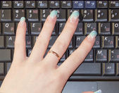 Girls hand laptop keyboard close up — Stock Photo