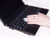 Girls hand on laptop keyboard — Stock Photo