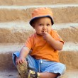 Orange dressed boy sitting on steps and — Stock Photo