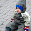 A boy in green snowsuit sitting on pavin — Stock Photo