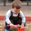 Child sitting in sandbox making mud pie — Stock Photo