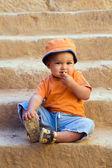 Orange dressed boy sitting on steps and — Stock Photo