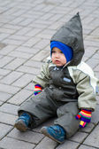 A boy in green snowsuit sitting on pavin — Stock Photo