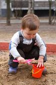 Child sitting in sandbox making mud pie — Stock Photo