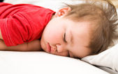 Boy in red dress sleeping on bed — Stock Photo