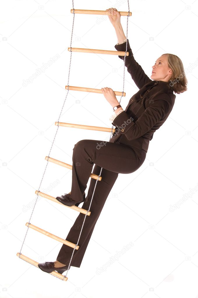 Young woman in brown suit climbering  the rope-ladder isolated on white  Stock Photo #1131636