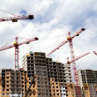 Building cranes and  building houses - Stock Photo