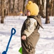 Thoughtful baby with shovel against snow — Stock Photo