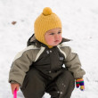 Royalty-Free Stock Photo: Thoughtful baby with shovel against snow
