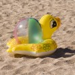 Stock Photo: Toy duck and ball againist sand